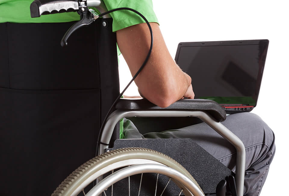 male student setting in wheelchair using a laptop